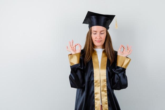 Jeune femme diplômée en tenue académique montrant un geste correct et à la vue de face, paisible.