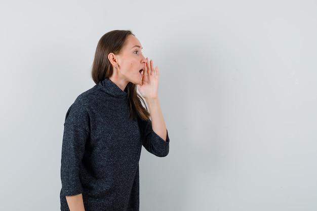 Jeune femme disant secret avec la main près de la bouche en chemise