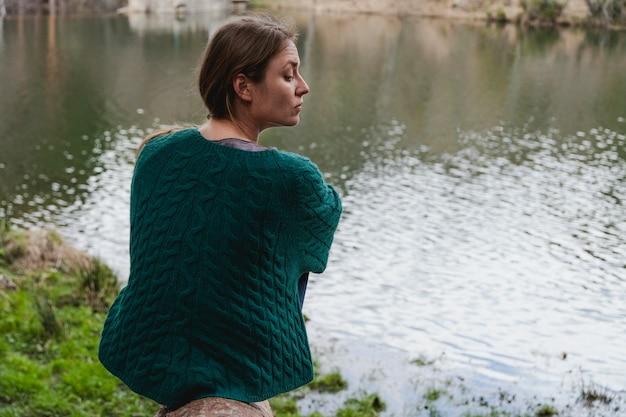 Jeune femme distrait assise près de la rivière
