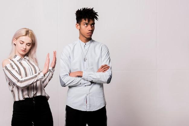 Jeune femme dit non à son petit ami en colère, debout contre le mur blanc