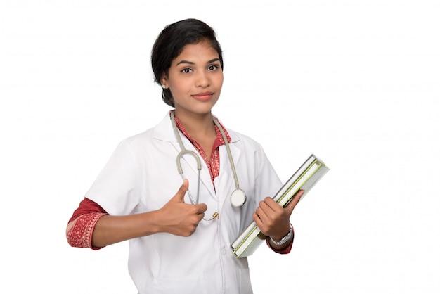 Jeune, femme, docteur, tenue, livre, stéthoscope