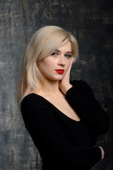 Jeune femme dodue blonde avec un maquillage lumineux en body noir pose