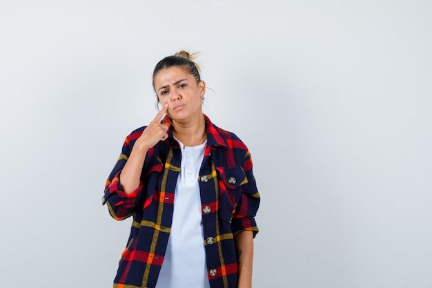 Jeune femme avec le doigt sur la joue en chemise à carreaux et l'air triste, vue de face.