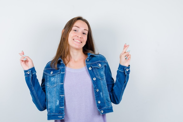Jeune femme avec les doigts croisés en veste en jean et à la gaieté. vue de face.