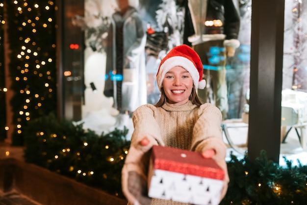 Jeune femme donnant une boîte pour vous en plein air dans la rue d'hiver concept d'échange de cadeaux.