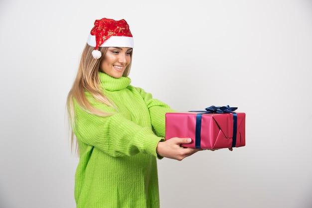 Jeune femme donnant un cadeau de noël festif.