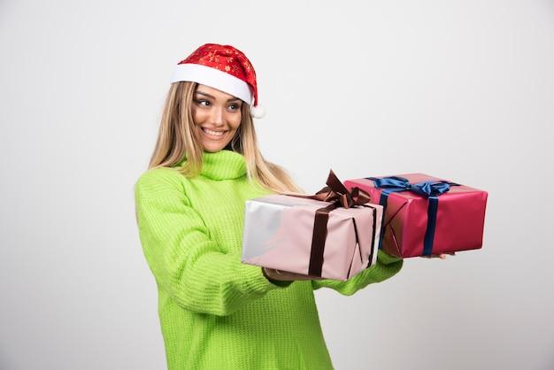 Jeune femme donnant des cadeaux de noël festifs.