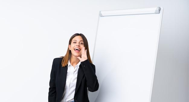 Jeune femme donnant une présentation sur un tableau blanc en criant avec la bouche grande ouverte