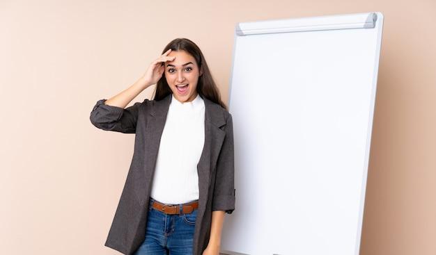 Jeune femme donnant une présentation sur tableau blanc avec surprise et expression faciale choquée