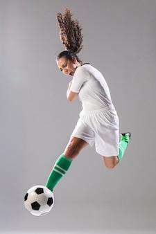 Jeune femme, donner coup pied, ballon de foot