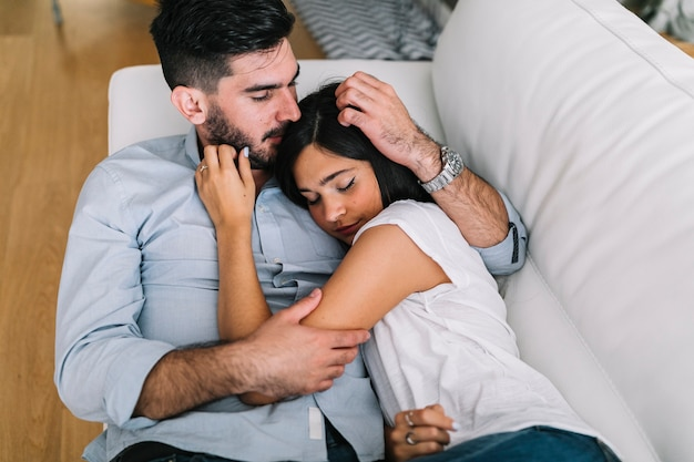 Jeune femme dormant avec son petit ami sur un canapé blanc