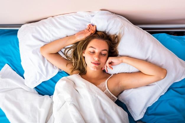 Jeune femme dort dans lit