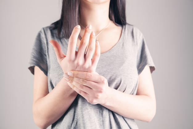 La jeune femme a la douleur de poignet sur le fond gris