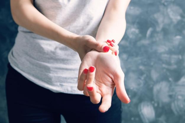 La jeune femme a la douleur de poignet sur le gris