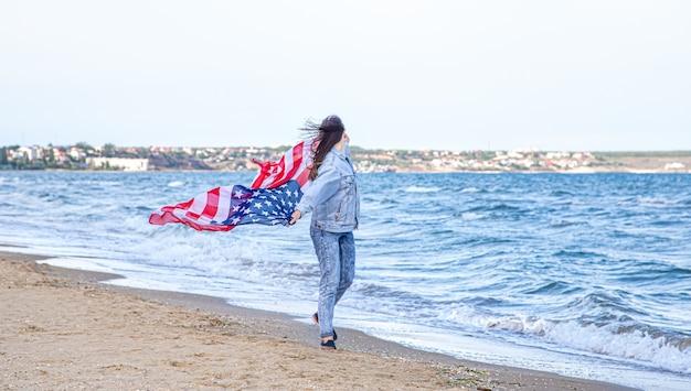 Une jeune femme avec un drapeau américain court au bord de la mer. le concept du patriotisme et des célébrations de la fête de l'indépendance.