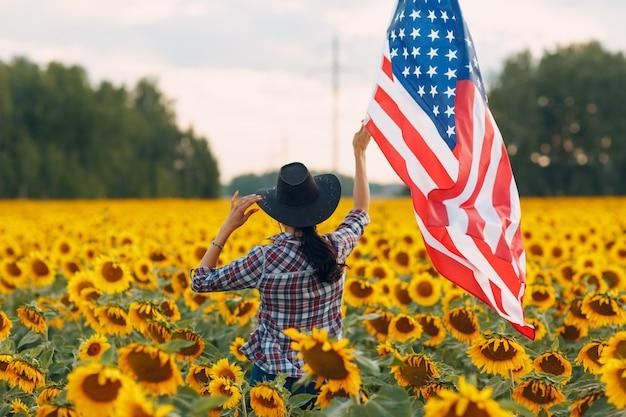 Jeune femme avec drapeau américain dans le champ de tournesol. concept de la fête de l'indépendance du 4 juillet aux états-unis.