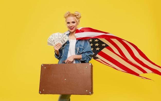 Une jeune femme avec un drapeau américain tient dans ses mains une valise de voyage et des billets en argent. visage joyeux surpris.