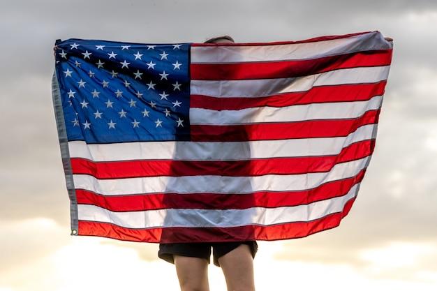 Jeune femme avec le drapeau des états-unis, profitant du coucher du soleil dans la nature.