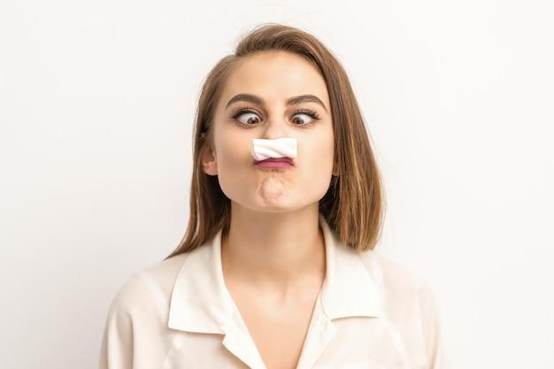 Jeune femme drôle avec des bonbons sucrés moustache guimauve. concept d'épilation et d'épilation