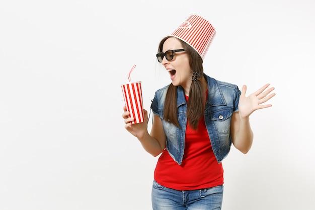 Jeune femme drôle dans des lunettes 3d avec seau pour pop-corn sur la tête en regardant un film, tenant une tasse en plastique de soda ou de cola, écartant les mains isolées sur fond blanc. émotions dans le concept de cinéma.
