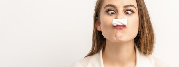 Jeune femme drôle avec une moustache sucrée ressemblant à une guimauve sur fond blanc concept d'épilation et d'épilation