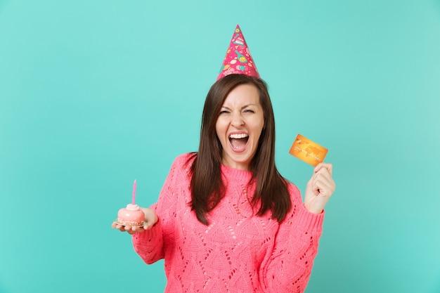 Jeune femme drôle en pull rose tricoté, chapeau d'anniversaire criant tenant à la main un gâteau avec une carte de crédit bougie isolée sur fond de mur bleu turquoise. concept de mode de vie des gens. maquette de l'espace de copie.