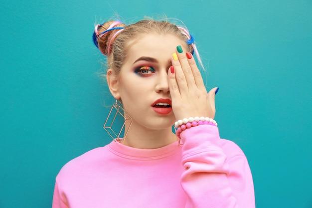 Jeune femme avec du maquillage arc-en-ciel sur fond de couleur