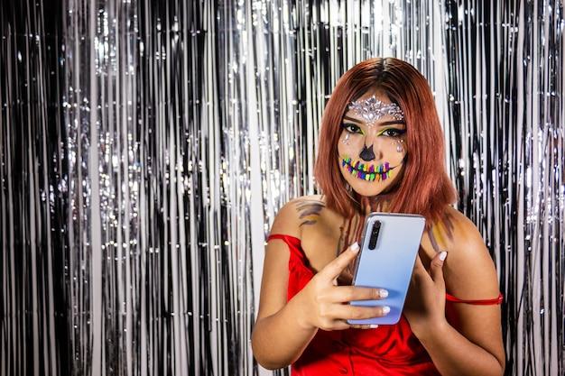 Jeune femme avec du maquillage pour la fête d'halloween fond noir et blanc lumineux téléphone portable à la main