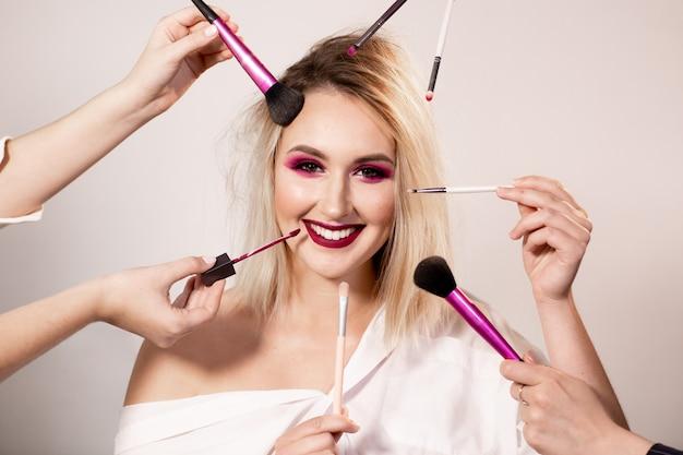 Jeune femme avec du maquillage rose foncé brillant qui pose en studio. les maquilleurs tiennent divers pinceaux pour le maquillage et le rouge à lèvres autour de son visage