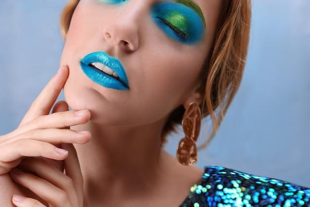Jeune femme avec du maquillage vert vif sur fond de couleur