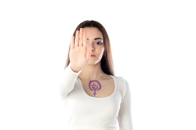 Jeune femme avec du maquillage violet et avec le concept d'activisme féministe s'appuyant sur son corps isolé