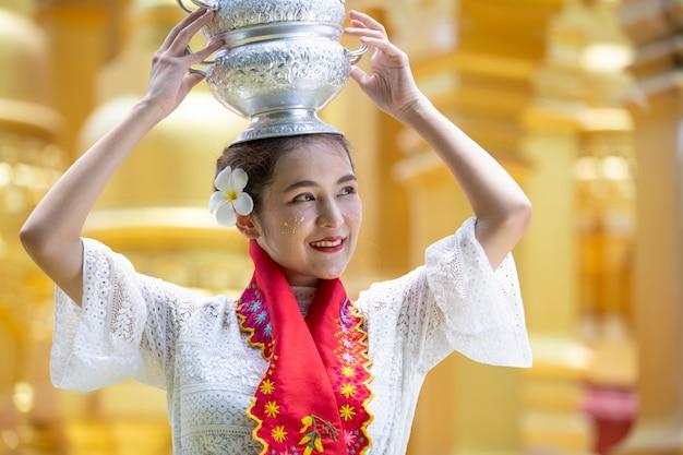 Une jeune femme du myanmar dans un geste d'accueil traditionnel avec la pagode shwedagon
