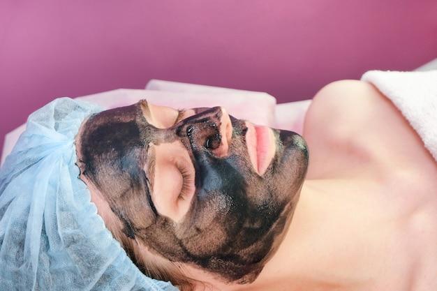 Jeune femme avec du nanogel de carbone sur son visage dans le salon. procédure d'épluchage.