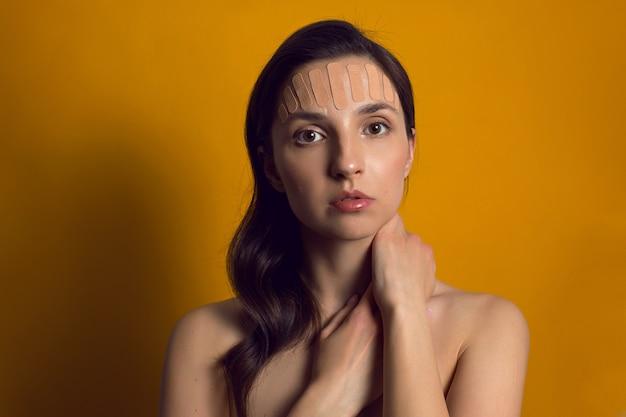 Jeune femme avec du ruban de kinésiologie marron sur le visage isolé