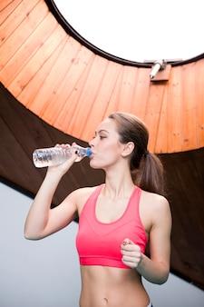 Jeune femme, eau potable, de, bouteille, dans, les, gymnase