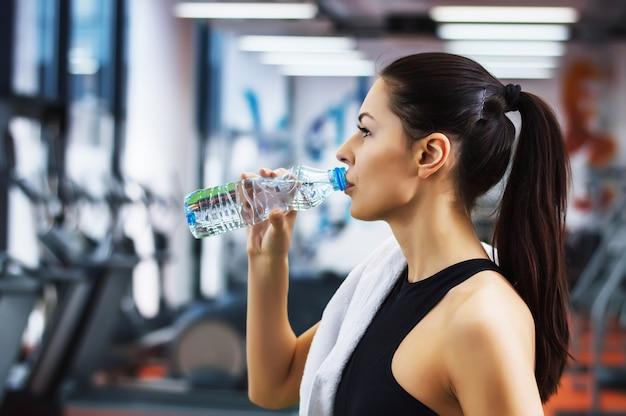 Jeune femme, eau potable, gymnase