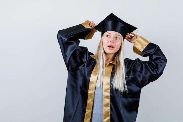 Jeune femme à l'écart en robe académique et à la surprise