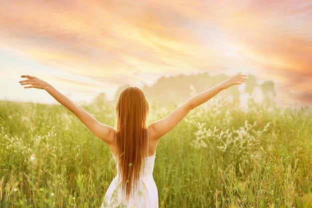 Jeune femme écartant les mains sur les côtés et face au soleil sur le terrain