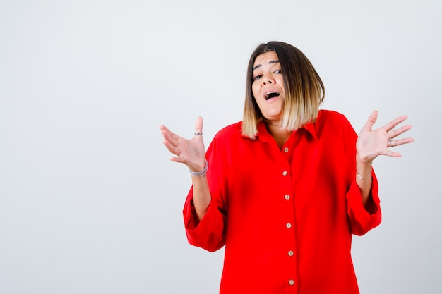 Une jeune femme écarte les paumes en chemise rouge surdimensionnée et a l'air étonnée, vue de face.