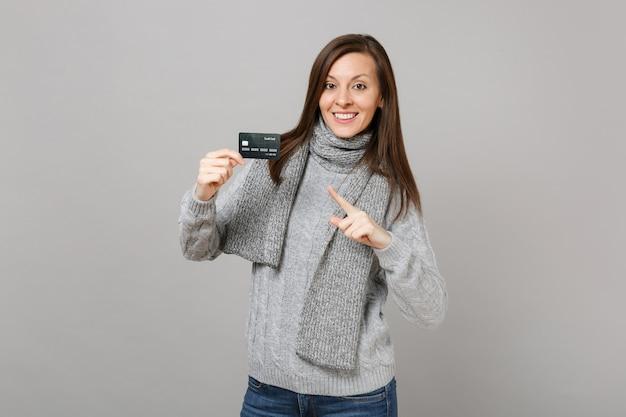 Jeune femme en écharpe pull gris pointant l'index sur la carte bancaire de crédit isolée sur fond de mur gris. les gens de mode de vie sain émotions sincères concept de saison froide. maquette de l'espace de copie.