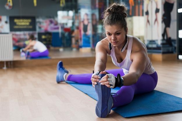 Jeune femme échauffement dans la salle de gym