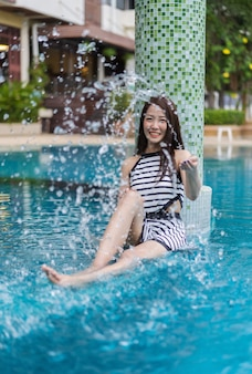 Jeune Femme éclabousser L'eau Dans La Piscine Photo Premium