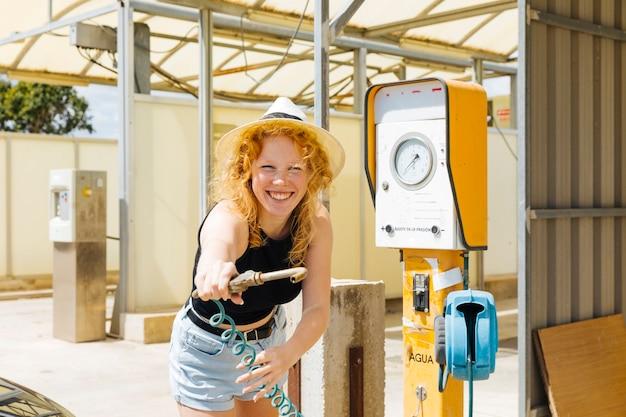 Jeune femme éclabousser avec le robinet d'eau à la station d'essence