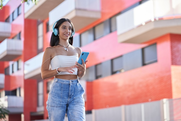 Jeune femme écoutant de la musique avec un casque et un smartphone dans la rue