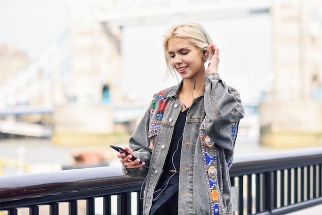 Jeune femme écoutant de la musique en contexte urbain.