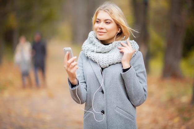 Jeune femme écoutant de la musique dans la forêt d'automne