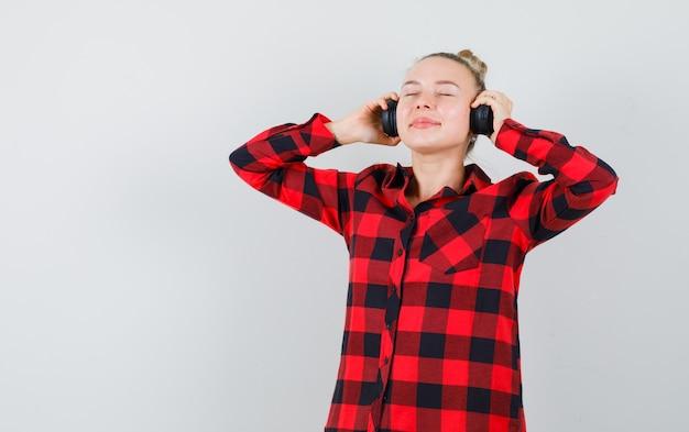 Jeune femme écoutant de la musique avec des écouteurs en chemise à carreaux et à la ravie. vue de face.