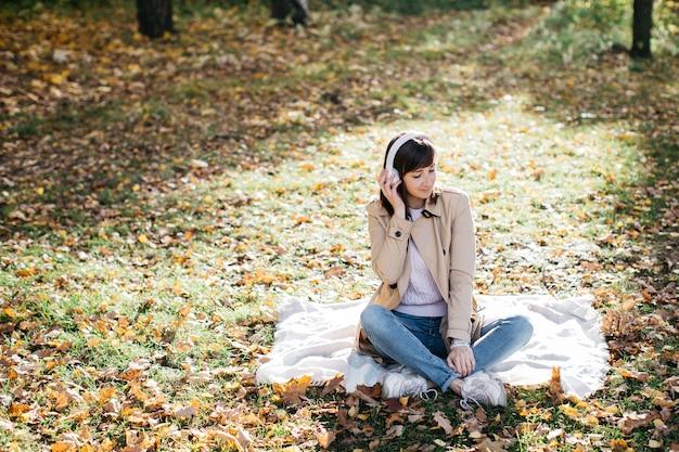 Jeune femme écoutant de la musique avec des écouteurs dans la forêt d'automne