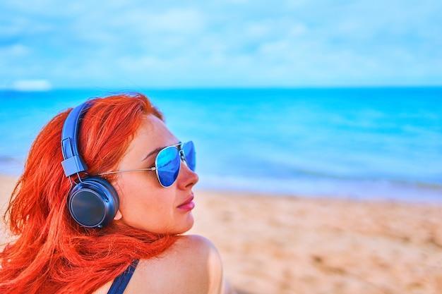 Jeune femme écoutant de la musique avec des écouteurs sur fond d'océan