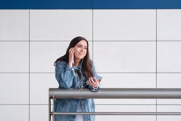 Jeune femme écoutant de la musique avec des écouteurs s'appuyant sur une balustrade. cheveux noirs. lumière naturelle du jour. mur blanc. copie espace